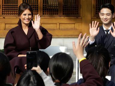 Ibu Negara AS, Melania Trump ditemani personel boyband SHINee, Choi Min-ho menghadiri acara 'Girls Play 2!', kampanye Olimpiade Musim Dingin PyeongChang 2018, di Kedutaan Besar AS di Seoul, Korea Selatan, Selasa (7/11). (AP Photo/Ahn Young-joon. Pool)