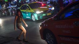 Foto pada 11 Oktober 2018 menunjukkan seorang wanita menyebrang jalan di Nana Red Light Distrik, Bangkok, Thailand. Nana Red Light District memang dikenal sebagai kawasan hiburan malam terbesar di Bangkok. (Romeo GACAD / AFP)