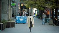 Seorang pria yang mengenakan masker berjalan di sepanjang Jerusalem Avenue yang hampir kosong di Warsawa tengah, Polandia (20/4/2020). Pemerintah Polandia telah melonggarkan beberapa kebijakan pembatasan terkait pandemi COVID-19 pada Senin (20/4). (Xinhua/Jaap Arriens)