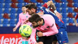 Striker Levante, Enis Bardhi (atas) berebut bola dengan bek Barcelona, Gerard Pique dalam laga lanjutan Liga Spanyol 2020/2021 pekan ke-36 di Ciutat de Valencia Stadium, Valencia, Selasa (11/5/2021). Levante bermain imbang 3-3 dengan Barcelona. (AFP/Jose Jordan)