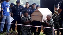 Petugas kepolisian Malaysia membawa peti mati jenazah yang di duga etnis Rohingya ke pemakaman massal di Alor Setar, Malaysia, Senin (22/6/2015).  21 dari 106 jenazah tak dikenal yang ditemukan bulan lalu dimakamkan hari ini. (Reuters/Olivia Harris)