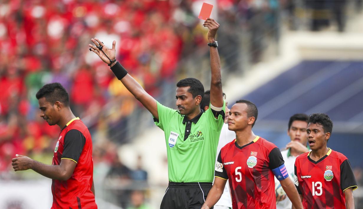 Pemmain Timor Leste, Filipe Oliveira (kiri) diusir wasit, Nagor Amir Amir Bin Noor Mohamed saat melakukan pelanggarann terhadap pemain Indonesia pada laga grup B SEA Games di Selayang, Malaysia (20/8/2017). Indonesia menang 1-0. (AP/Adrian Hoe)