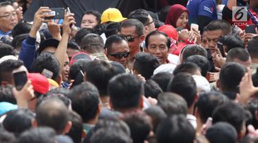 Presiden Joko Widodo (tengah) berjalan menembus kerumunan warga usai peresmian pengoperasian Moda Raya Terpadu Jakarta fase 1 di Kawasan Bundaran HI, Jakarta, Minggu (24/3). Acara ini sekaligus pencanangan pembangunan Moda Raya Terpadu Jakarta fase 2. (Liputan6.com/Helmi Fithriansyah)