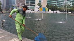 Petugas membersihkan kolam Patung Selamat Datang di kawasan Bundaran HI, Jakarta, Kamis (23/8). Pembersihan dilakukan dalam rangka perawatan rutin guna menjaga keindahan estetika kota. (Liputan6.com/Immanuel Antonius)