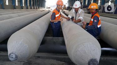 Pekerja menyelesaikan tahap akhir pembuatan precast tiang pancang beton di PT Waskita Beton Precast Plant Prambon, Sidoarjo, Jawa Timur, Kamis (21/11/2019). Plant Prambon memproduksi spun pile, pci girder dan ccsp bagi kebutuhan proyek Jalan Tol Trans Jawa. (Liputan6.com/HO/Eko)