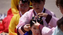 """Seorang wanita muda melakukan ritual penyematan ornamen kepala selama upacara """"Coming of Age"""" di Namsan Hanok Village, Seoul, Senin (20/5/2019). Di Korea Selatan, Coming of Age Day atau hari kedewasaan dirayakan secara nasional setiap tahun pada hari Senin ketiga di bulan Mei. (Ed JONES/AFP)"""