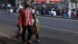 Seorang pria dan seorang anak berjalan saat umat muslim melaksanakan salat Idul Adha 1442 H di Masjid Masjid Jami Al-Mubarok, Tangerang, Banten, Selasa (20/7/2021). Sebagian masjid melakukan pelaksanaan salat Idul Adha 1442 H, namun dengan protokol kesehatan yang ketat. (Liputan6.com/Angga Yuniar)