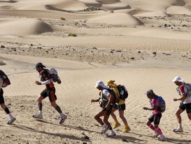 Peserta mengambil bagian dalam lomba lari internasional Marathon des Sables ke-32 tahap ketiga di Gurun Sahara, sebelah selatan Maroko, Selasa (11/4). Maraton ini menempuh jarak 250 km melintasi Gurun Sahara yang panas ekstrem. (JEAN-PHILIPPE KSIAZEK/AFP)