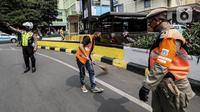 Warga pelanggar Pembatasan Sosial Berskala Besar (PSBB) dihukum menyapu jalanan saat terjaring razia masker di wilayah Tanah Abang, Jakarta, Senin (14/9/2020). Razia tersebut guna menekan kasus penyebaran COVID-19 di Jakarta pada masa PSBB. (Liputan6.com/Johan Tallo)