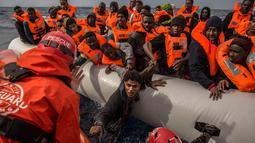 Petugas dari LSM Spanyol Proactiva Open Arms saat menyelamatkan pengungsi dan imigran setelah meninggalkan Libya yang mencoba mencapai tanah Eropa, 60 mil sebelah utara Al -Khum, Libya (18/2). (AP Photo/Olmo Calvo)