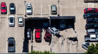 Sebuah tempat parkir dua lantai runtuh di Irving, Texas, Selasa (31/7). Masih belum jelas apa yang menyebabkan lantai tersebut roboh dan menimpa kendaraan lain di bawahnya. (Ashley Landis/The Dallas Morning News via AP)