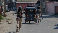 Seorang tentara paramiliter India membawa batu selama bentrok dengan pengunjuk rasa selama protes terhadap pembunuhan pemberontak di Srinagar, Kashmir yang dikuasai India, (1/4). (AP Photo / Dar Yasin)