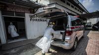 Petugas kesehatan menyiapkan peti mati berisi korban virus corona COVID-19 ke dalam ambulans di Bogor, Jawa Barat pada 3 Juli 2021. Angka kematian pasien Covid-19 saat isolasi mandiri di Indonesia sangat mengkhawatirkan di saat kasus semakin melonjak. (AFP/ Aditya Aji)