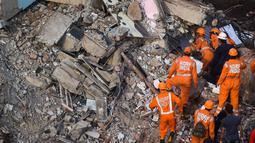 Petugas penyelamat mencari orang-orang di reruntuhan gedung apartemen berlantai lima yang runtuh di Mahad, India (25/8/2020). Polisi menyebut bangunan ini terdiri dari 47 flat. Sekitar 120 kilometer sebelah selatan Mumbai. (AFP Photo/Punit Paranjpe)