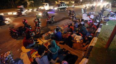 Pemudik menyempatkan beristirahat di pinggir jalan Kota Cirebon karena kelelahan berkendara dari Jakarta, Jumat (24/6). Mereka beristirahat sambil mendinginkan kendaraan bermotor. (Liputan6/JohanTallo)