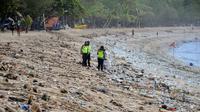 Polisi berdiri di antara sampah kiriman yang terdampar memenuhi pesisir pantai Kuta, Bali, Kamis (31/12/2020). Menjelang pergantian tahun baru, Pantai Kuta hanya terlihat beberapa wisatawan, namun tumpukan sampah kiriman tersebar di sepanjang bibir pantai. (SONNY TUMBELAKA / AFP)