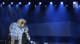 Penyanyi Muhammad Tulus Rusydi atau Tulus tampil bersama sebuah boneka dalam konser Monokrom di Istora Senayan, Jakarta, Rabu (6/2). Boneka ini merupakan bagian dari atraksi visual Pappermoon Puppet Theater dari Yogyakarta. (Fimela.com/Bambang Eros)