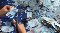 PNS menggunting E-KTP untuk dihancurkan di Gundang Kemendagri, Bogor (30/5). Ratusan ribu E-KTP ini dihancurkan dengan cara digunting. (Merdeka.com/Arie Basuki)