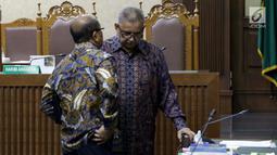 Terdakwa dugaan suap proyek PLTU Riau-1 yang juga mantan Dirut PLN, Sofyan Basir bersama kuasa hukumnya jelang sidang lanjutan di Pengadilan Tipikor, Jakarta, Senin (26/8/2019). Sidang mendengar keterangan saksi ahli yang dihadirkan JPU KPK. (Liputan6.com/Helmi Fithriansyah)
