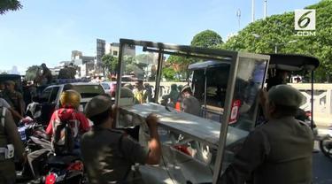 Seorang pedagang kaki lima memaki petugas Satpol PP karena tidak terima barang dagangannya disita petugas