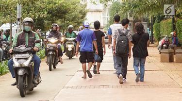 Pengendara sepeda motor melintasi trotoar di kawasan Menteng Pulo, Jakarta, Selasa (14/5/2019). Kemacetan yang semakin parah di Ibu Kota menyebabkan para pemotor nekat menerobos trotoar dan merampas hak pejalan kaki. (Liputan6.com/Immanuel Antonius)