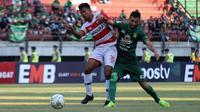 Zulfiandi (Madura United) duel melawan  Manuchehr Jalilov (Madura United) dalam laga leg pertama perempat final Piala Indonesia 2018 di Stadion Gelora Bung Tomo, Surabaya, Rabu (19/6/2019). (Bola.com/Aditya Wany)