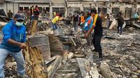 masyarakat dibantu TNI Polri membersihkan material rusuh Wamena. 9Liputan6.com/Pendam Cenderawasih/Katharina Janur)