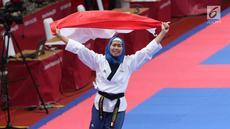 Atlet Taekwondo putri Indonesia, Defia Rosmaniar mengibarkan bendera Merah Putih saat merayakan kemenangan atas Salahshouri Marjan (Iran) pada Final Women Individual Poomsae di JCC, Jakarta, Minggu (19/8). (Liputan6.com/Helmi Fithriansyah)