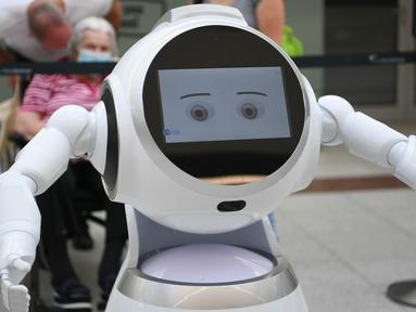 Para pengunjung mengamati sebuah robot pintar yang menjelaskan tentang langkah-langkah pencegahan COVID-19 di sebuah pusat perbelanjaan di Frankfurt, Jerman, pada 12 September 2020. (Xinhua/Lu Yang)