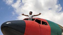 Seorang pemuda berdiri melalui kanopi kosong pesawat Boeing 707 yang diubah oleh saudara kembar Palestina Atallah dan Khamis al-Sairafi menjadi sebuah restoran di kota Nablus, pada 5 Juli 2021. Restoran bertema penerbangan itu dihiasi dengan bendera Palestina dan Yordania (JAAFAR ASHTIYEH/AFP)