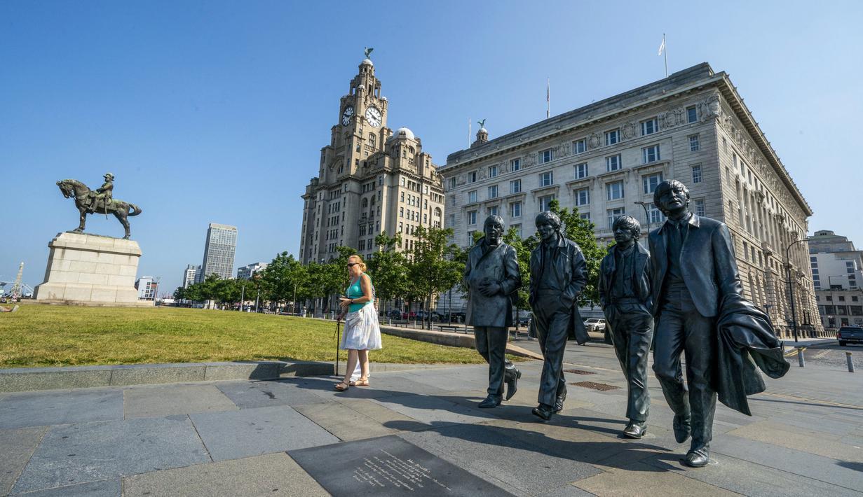 Patung The Beatles dan Royal Liver Building di tepi pantai Liverpool, Rabu (21/7/2021). Kota Liverpool Inggris telah dihapus dari daftar situs warisan dunia UNESCO karena hadirnya bangunan baru, termasuk stadion baru klub bola Everton, yang merusak daya tarik dermaga Victoria. (Peter Byrne/PA via AP