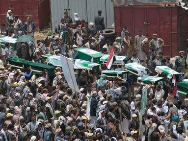 Orang-orang membawa peti jenazah puluhan bocah di Yaman korban serangan koalisi Arab Saudi, pada pemakaman di Saada, Senin (13/8). Pemakaman diwarnai protes terhadap Saudi yang dinilai bertanggung jawab atas kematian anak-anak tersebut. (AP/Hani Mohammed)