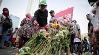 """Pengunjung car free day menaburkan bunga di atas papan bertuliskan """"Terima Kasih Pejuang Demokrasi"""" di Bundaran HI, Jakarta, Minggu (28/4/2019). Kegiatan tabur bunga tesebut sebagai bentuk belasungkawa atas meninggalnya petugas KPPS dalam Pemilu 2019. (Liputan6.com/Faizal Fanani)"""