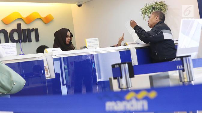 Nasabah melakukan transaksi di cabang Bank Mandiri Pertamina UPMS III, Jakarta, Rabu (28/6). Bank Mandiri memberikan layanan perbankan terbatas kepada nasabah secara bergantian pada musim liburan Idul Fitri 26-30 Juni 2017. (Liputan6.com/Angga Yuniar)