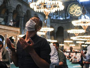 Umat Muslim, mengenakan masker sebagai pencegahan penyebaran COVID-19, berkumpul untuk salat Idul Adha di dalam era Bizantium Hagia Sophia, yang baru-baru ini dikonversi kembali ke masjid, di distrik bersejarah Sultanahmet Istanbul, Turki pada 31 Juli 2020. (Pool via AP)