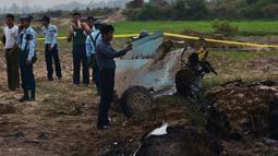Tentara Myanmar menjaga reruntuhan jet tempur yang jatuh di area persawahan desa Kyunkone, berjarak satu jam dari ibu kota Naypyidaw, Selasa (3/4). Pihak kepolisian mengatakan pesawat yang jatuh merupakan tipe F-7 dengan kemudi tunggal. (AFP Photo)