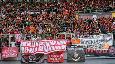 Suporter Persija Jakarta memasang spanduk protes saat pertandingan melawan Perseru Badak Lampung pada laga Liga 1 2019 di Stadion Patriot, Bekasi, Minggu (1/9). Persija takluk 0-1 dari Badak Lampung. (Bola.com/M Iqbal Ichsan)