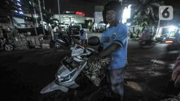 Salah satu pembeli bungkus atau tali ketupat di Pasar Klender, Jakarta Timur, Selasa (11/5/2021) malam. Biasanya empat hari menjelang Lebaran pedagang ketupat musiman tersebut mulai bermunculan menjajakan bahan baku makanan khas Idul Fitri ini. (merdeka.com/Iqbal S Nugroho
