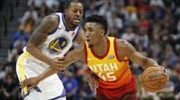 Aksi pemain Utah Jazz, Donovan Mitchell (kanan) mencoba melewati adangan pemain Warriors, Andre Iguodala pada lanjutan NBA basketball game di Vivint Smart Home Arena, Salt Lake City, (30/1/2018). Utah menang 129-99. (AP/Rick Bowmer)