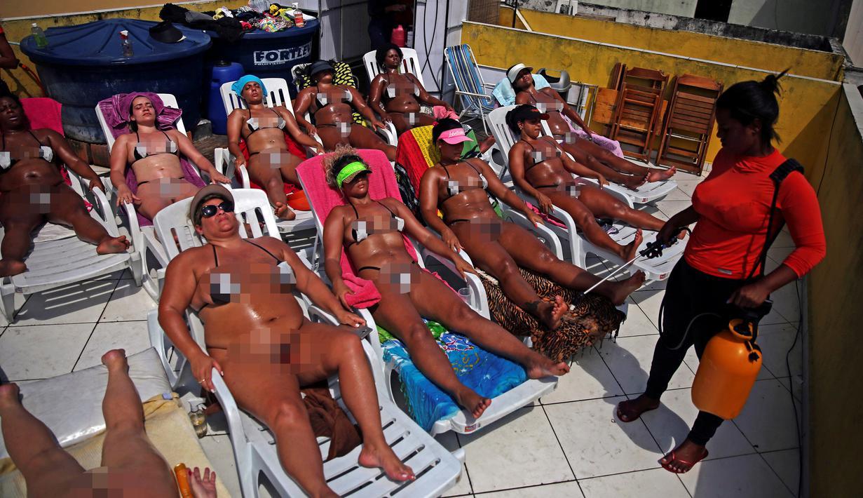 Sejumlah pengunjung berjemur saat melakukan spa di Rio de Janeiro, Brasil (22/11). Mereka berjemur untuk mendapatkan tanda bikini yang sempurna di tubuhnya, atau yang biasa disebut dalam bahasa Portugis Marquinha. (Reuters/Pilar Olivares)