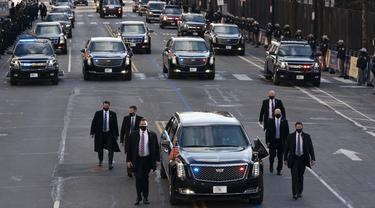 Mobil Presiden Amerika Serikat (AS), Joe Biden dalam pengawalan melintas di 15th street menuju Gedung Putih di Washington, Rabu (20/1/2020). Joe Biden menggunakan mobil dinas yang sama dengan yang digunakan oleh Presiden sebelumnya, Donald Trump yaitu Cadillac One. (Jose Luis Magana/POOL/AFP)