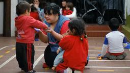 Noelia Garella bermain dengan muridnya di TK Jeromito, Argentina (24/10). Keinginan Noelia menjadi guru TK berawal dari masa kecil yang pahit saat dirinya ditolak masuk ke sebuah sekolah, bahkan dirinya disebut 'Monster'. (AFP Photo/Diego Lima)