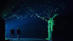 """Pengunjug berada di dekat seni instalasi cahaya """"Painting the Night"""" karya seniman Austria Victoria Coeln saat hujan turun di taman Heruerhae Gaerten di Hanover, Jerman utara, (4/5). (AFP Photo/dpa/Silas Stein/Jerman Out)"""