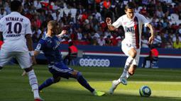 Gelandang PSG, Angel Di Maria, berusaha melewati pemain Strasbourg pada laga Liga 1 Prancis di Stadion Parc des Princes, Sabtu (14/9). PSG menang 1-0 atas Strasbourg. (AP/Francois Mori)