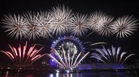 Kembang api meledak di atas kincir London Eye Ferris di Sungai Thames di London, untuk menandai awal tahun baru, Rabu (1/1/2020). (AP Photo/Matt Dunham)