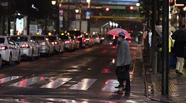 Seorang pria melintasi persimpangan menuju stasiun kereta api di Tokyo, Jumat (5/3/2021).  PM Jepang Yoshihide Suga mengumumkan bahwa pemerintahnya memperpanjang keadaan darurat di wilayah Tokyo selama dua minggu lagi untuk mencegah terjadinya lonjakan infeksi COVID-19. (AP Photo/Hiro Komae)