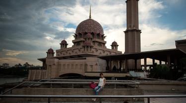 Gambar yang diambil pada 22 November 2017, memperlihatkan seorang turis berpose di depan masjid berwarna pink di kawasan Putrajaya, Malaysia. Masjid Putra ini terdiri dari 4 lantai yang dilengkapi dengan lift. (MANAN VATSYAYANA/AFP)