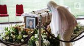 Seorang wanita berada dekat peti jenazah almarhum Ketua Umum Pengurus Besar Persatuan Atletik Seluruh Indonesia (PB PASI) Bob Hasan di Jakarta, Selasa (31/3/2020). Bob Hasan meninggal dunia di RSPAD Gatot Subroto Jakarta setelah sempat dirawat intensif selama tiga bulan. (Liputan6.com/Faizal Fanani)