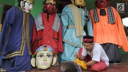 Perajin menyelesaikan pembuatan ondel-ondel Betawi ukuran besar di Serpong, Tangerang Selatan, Banten, Rabu (10/10). Selain Jabodetabek, permintaan kerajinan ondel-ondel juga datang dari Australia. (Merdeka.com/Arie Basuki)