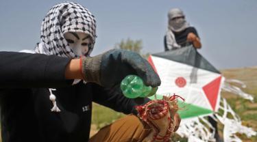 Warga Palestina menyiapkan bom molotov untuk diterbangkan menggunakan layang-layang di atas pagar perbatasan dengan Israel, di pinggiran timur Kota Gaza (20/4). Unjuk rasa warga Palestina terhadap Isrel memasuki minggu keempat. (AFP Photo/Mohammed Abed)